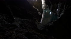 Tilt up to sun filled hole in mysterious cave Stock Footage