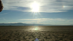 A man walks into the rising sun in a harsh desert landscape - stock footage