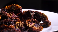 Rotating white plate with sundried tomatoes on black background Stock Footage