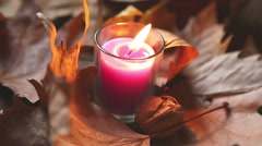 Candle surrounded by leaves that  with a gust of wind comes off Stock Footage