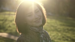 Young woman outdoor portrait in soft sunny daylight - stock footage