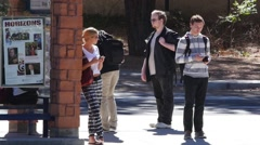 Students wait for a bus on campus Stock Footage