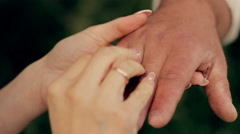 bride groom wears the ring at sunset in the park - stock footage
