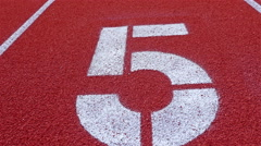 Slow dolly of a number 5 on a running track, counter number five Stock Footage