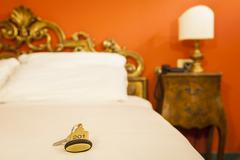 Hotel Room Key lying on Bed with keyring - stock photo
