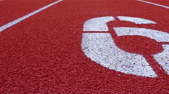 Slow dolly of a number 6 on a running track, counter number six Stock Footage