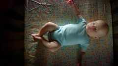 Single Caucasian Baby lying in crib on pretty sheet getting ready to go to bed Stock Footage