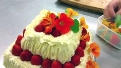 Stock Video Footage of Decorating a strawberry cake, with edible flowers