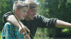 4K Man and young boy spending time together and fishing at lake - stock footage