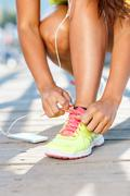 Running shoes - woman tying shoe laces. Closeup of female sport fitness runne - stock photo