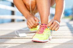 Running shoes - woman tying shoe laces. Closeup of female sport fitness runne Stock Photos