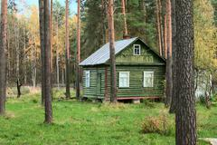 wooden cottage in forest - stock photo