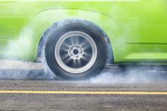 race car burns rubber off its tires - stock photo
