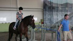 Girl training a horse, trainer trains girl horseback riding Stock Footage