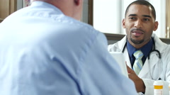 Doctor discussing prescription drugs with male patient Stock Footage
