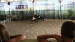 children watch a horse show, back view - stock footage