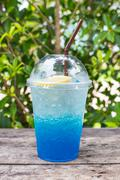 blue lemon soda on wood table with green leaves background, be fresh in natur - stock photo