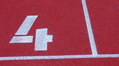 Slow dolly of a number 4 on a running track, counter number four Stock Footage