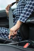 Closeup of woman hand fastening a seat belt in the car - stock photo