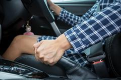 Closeup of young woman pulling handbrake lever in car Kuvituskuvat
