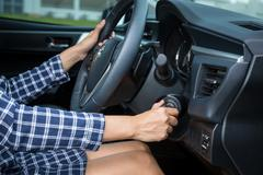 Women driver hand inserting car key and starting engine. - stock photo