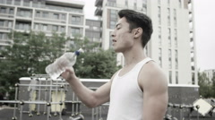 4K Asian man working out in outdoor urban environment takes a break to rehydrate Stock Footage