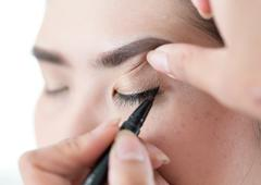 Makeup beauty with brush eye liner on pretty woman Stock Photos