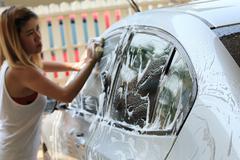 Car wash, woman washing car at home Kuvituskuvat