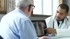 Doctor showing x ray to senior male patient - stock footage