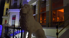 A lion statue sits in front of an elegant row of houses and a pub in a British - stock footage
