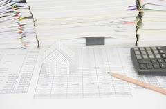House and pencil have paperwork with books as background - stock photo