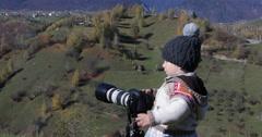 Cute child photographs the nature, autumn mountain landscape - stock footage