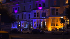 Victorian houses, pubs and hotels are lit at night in an English town. - stock footage