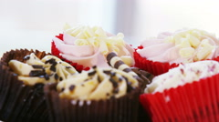 Stock Video Footage of 4K Close up on a plate of colourful frosted cupcakes