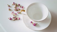 Pour tea in a beautiful white cup with lemon and roses Stock Footage