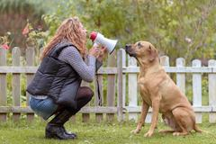 Young woman talking to her dog on a megaphone Kuvituskuvat