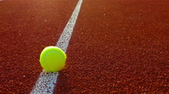 Tennis balls are rolling along court line Stock Footage