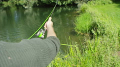 4K Young man fishing at lake, casting his line into the water - stock footage