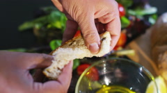 4K Hands breaking bread and dipping a piece into fresh dressing - stock footage