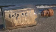 """Seascape with  bottle with a message """"help me"""" in sand - stock footage"""