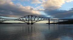 Train crossing Forth Rail Bridge at dawn Scotland Stock Footage