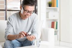 Asian man eating supplement Stock Photos