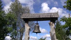 Metal bell hanging under wooden park gate roof Stock Footage