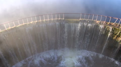 Water flowing through dam with fog rising in morning Stock Footage