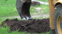 Industrial  excavator digging a hole on lawn Stock Footage