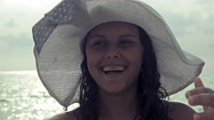 Vintage 4k shot of Shy Happy Girl With Hat Loughing on Beach Stock Footage