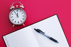 alarm clock with notepad - stock photo