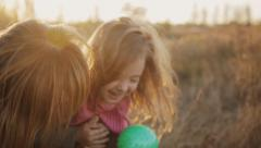 Little girl with mother laughing and kissing in the sunset light Stock Footage