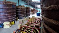 Fish sauce factory camera tilts up showing filled bottles and production tubs 4k Stock Footage