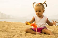 Beautiful baby sits facing the camera and playing  with toy rake on the beach. Stock Photos